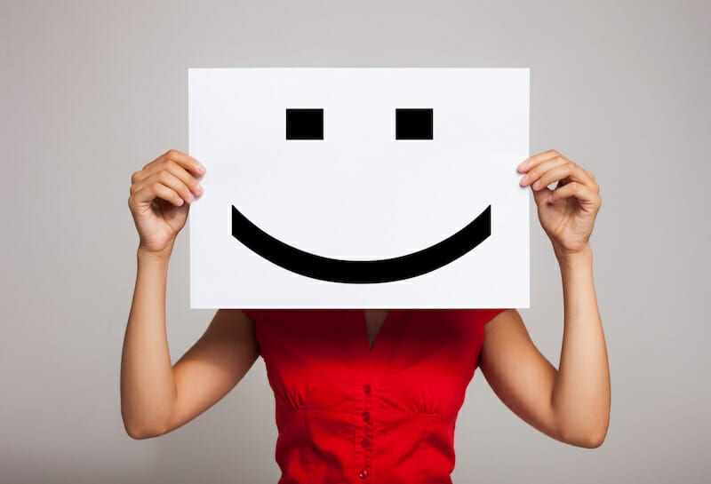 woman holding smiley face in front of her face