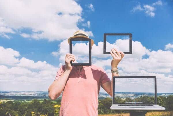 Man holding computer and tablet behind skies