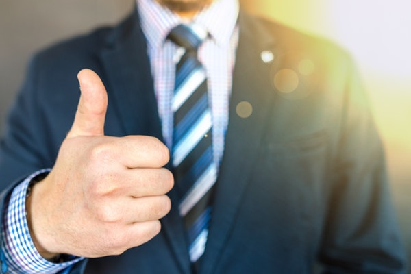 Man in suit holding up a thumbs-up