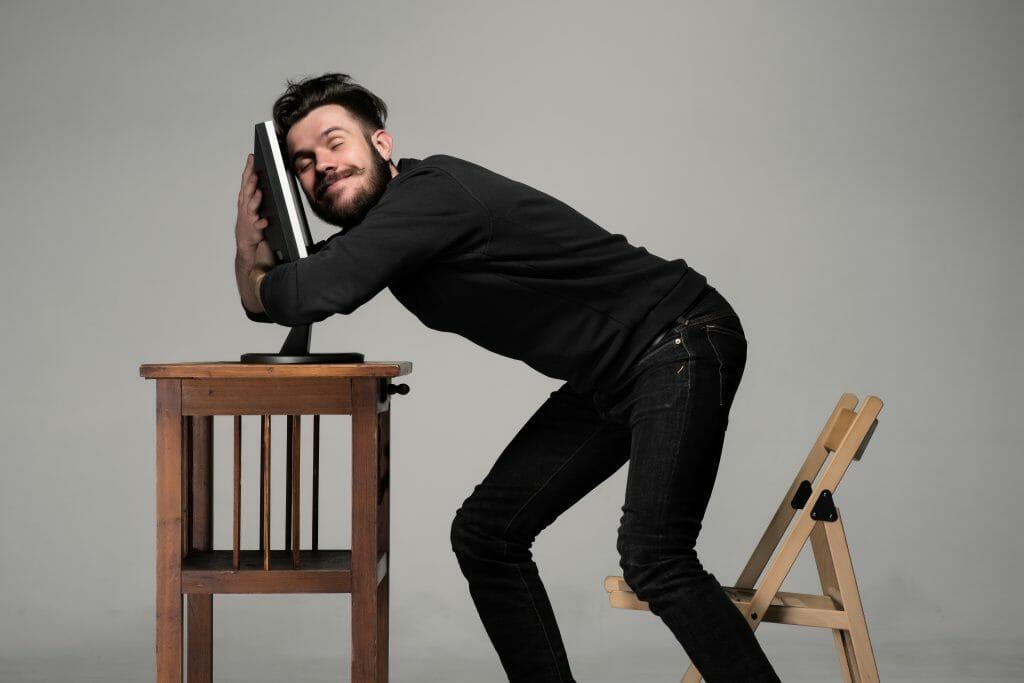 Man hugging computer