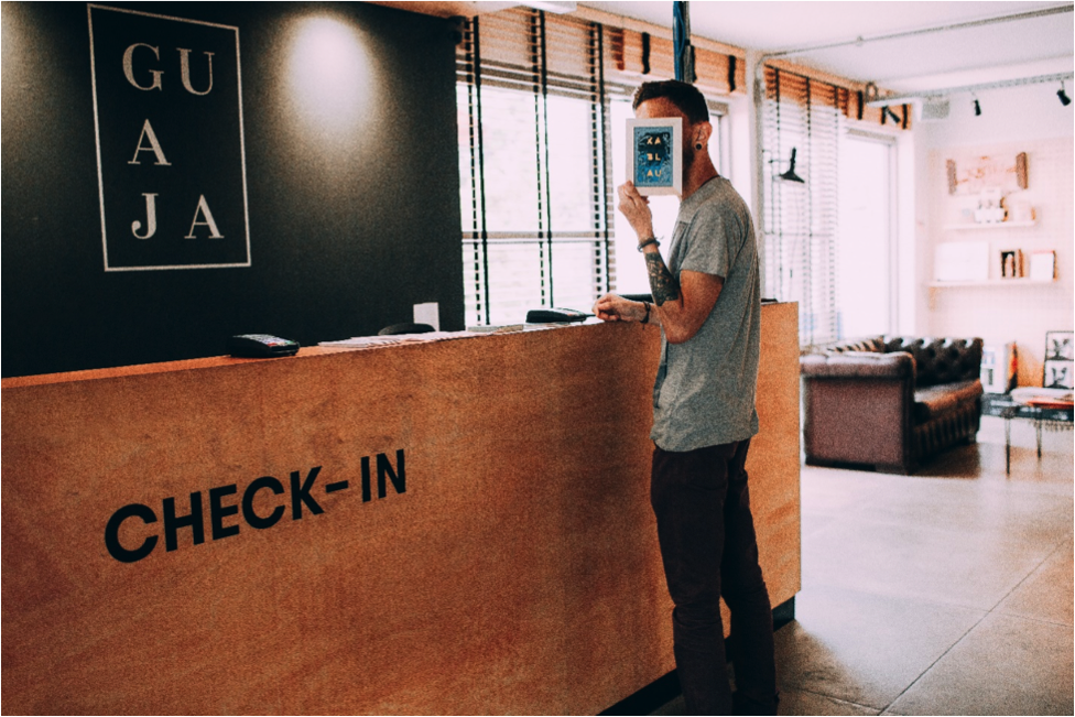 Man holding postcard at check-in at a hotel