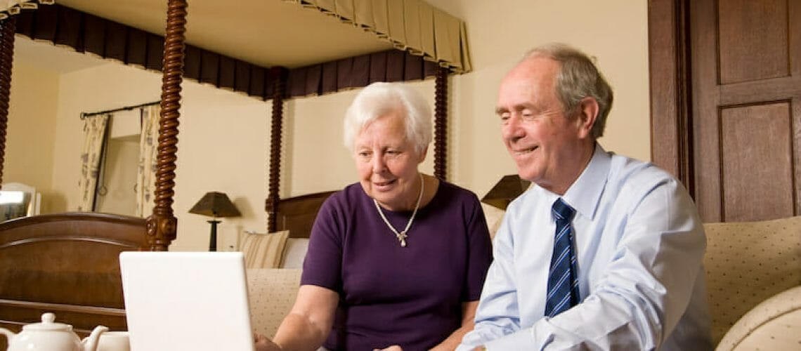 Happy senior couple using laptop in luxurious hotel bedroom suite