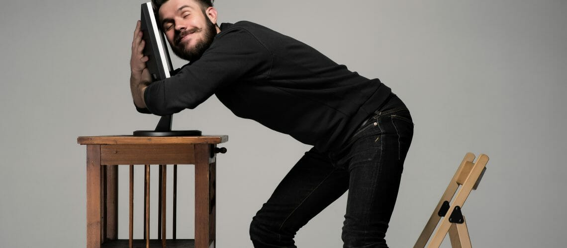 Funny and crazy man using a computer on gray background. human hands hug monitor. Concept of love to computer